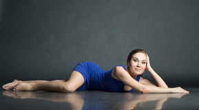Woman in blue short dress lying on dark background Royalty Free Stock Image