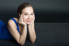 Woman in blue short dress lying on dark background Stock Photography