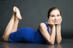 Woman in blue short dress lying on dark background Royalty Free Stock Images
