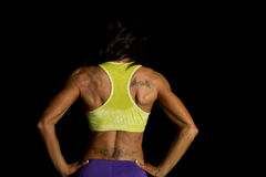 Woman blue shorts and green sports bra on black back hands hips. A woman with her hands on her hips, and her tattoos on her back royalty free stock image