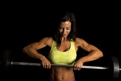 Woman blue shorts and green sports bra on black barbell look dow Royalty Free Stock Photography