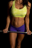 Woman blue shorts and green sports bra on black hold bar by wais Stock Image