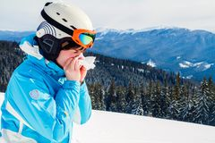 A woman in a blue ski suit is holding a handkerchief and wiping her nose. Skier with cold royalty free stock image