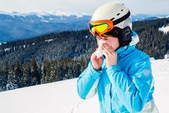 A woman in a blue ski suit is holding a handkerchief and wiping her nose. Skier with cold stock image