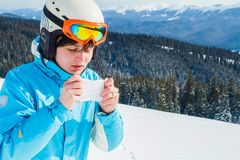 A woman in a blue ski suit is holding a handkerchief and wiping her nose. Skier with cold royalty free stock photography