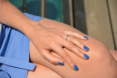 Woman in blue skirt sitting on a bench. Blue manicure royalty free stock photo
