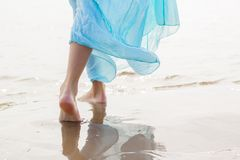 Woman with blue skirt walking on the beach. In sunny day Royalty Free Stock Photography