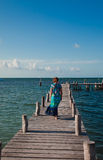 Woman in blue, sky and sea. Woman standing on a pier and seeing at the sea Royalty Free Stock Image
