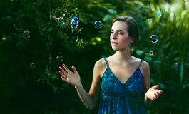 Woman in Blue Spaghetti Strap Dress Standing Near Green Plant Royalty Free Stock Image
