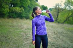 Woman in a blue sports jacket with a hood and black  leggins dri. A caucasian athletic  woman in a blue sports jacket with a hood and black  leggins drink water Stock Images