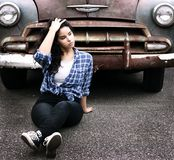 Woman in Blue Sports Shirt Sitting Infront of Vintage Brown Car Stock Image