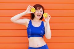 Woman in blue sports wear dances with two slice oranges and laughs. Fresh healthy lifestyle concept stock photo