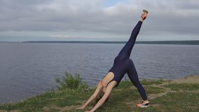 Woman in blue sportswear, yoga exercise outdoor stock photo
