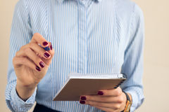 Woman in a blue striped shirt writing in a notebook Royalty Free Stock Photography