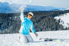 Woman in blue suit, helmet and glasses sits on the snow near the skis on top of the mountain royalty free stock photos