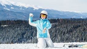 Woman in blue suit, helmet and glasses sits on the snow near the skis on top of the mountain stock image