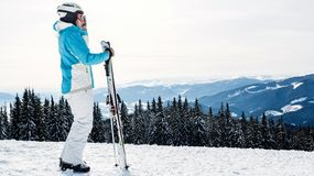 A woman in a blue suit, a helmet and glasses is standing with skis on top of a mountain royalty free stock photography