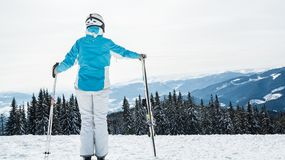 A woman in a blue suit, a helmet and glasses is standing with skis on top of a mountain royalty free stock image