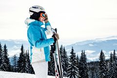 A woman in a blue suit, a helmet and glasses is standing with skis on top of a mountain royalty free stock photo