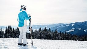 A woman in a blue suit, a helmet and glasses is standing with skis on top of a mountain stock photos