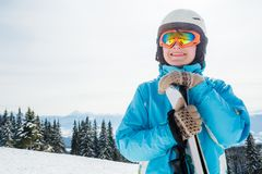 A woman in a blue suit, a helmet and glasses is standing with skis on top of a mountain royalty free stock images