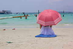 Woman in blue suit with red umbrella sat on the beach Royalty Free Stock Photography