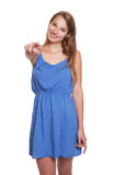 Woman in a blue summer dress pointing at camera Royalty Free Stock Image