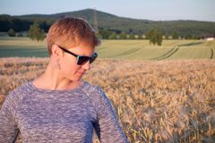 Woman with blue sunnglasses at sunset looking down in a corn field. Woman with blue sunnglasses at sunset and a corn field with a colorful pink sky and hills in stock photography