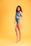 Woman in blue swim wear having fun with soap bubbles Stock Image