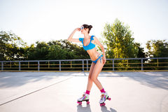 Woman in blue swimsuit riding on roller skates at park Royalty Free Stock Photography