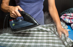 Woman in a blue T-shirt ironing plaid shirt and other clothing Stock Image