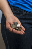 Woman in the blue t-shirt and jeans holds coins Royalty Free Stock Images
