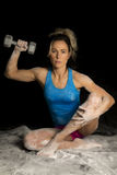 Woman in blue tank top sitting in powder holding up a weight Royalty Free Stock Photography