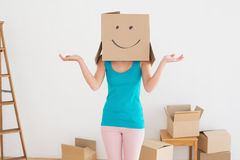 Woman in blue tank top with smiley cardboard box over face Royalty Free Stock Photo