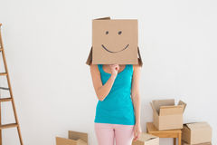 Woman in blue tank top with smiley cardboard box over face Stock Images