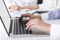 Woman in blue is typing while her colleague in the background is Stock Image