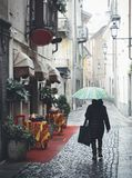 Woman with blue umbrella walks on quaint cobblestone alleyway in Aosta, Italy with inviting red carpet entrance to Italian restaur Royalty Free Stock Photo