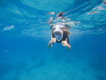 Woman in blue water. Female snorkel in full face mask and swim gear. Stock Images