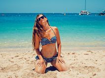 Woman In Blue And White Bikini Kneeling On Sand stock photography