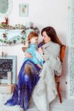 Woman in Blue White and Brown Dress Holding Baby in Teal Dress Inside House Royalty Free Stock Photography