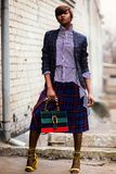 Woman in Blue and White Plaid Cardigan Holding Green and Red Handbag royalty free stock image