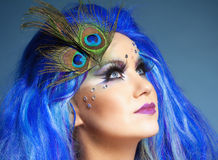 Woman in Blue Wig and Peacock Feathers Stock Photo