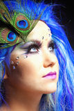 Woman in Blue Wig and Peacock Feathers Stock Image