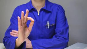 Woman in blue work uniform making the Okay sign stock video footage