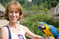 Woman with blue-and-yellow macaw. On her arm royalty free stock photography