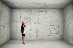 Woman with blueprint in empty room Stock Image