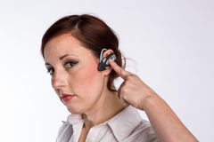Woman with Bluetooth Headset. A young business woman with red hair and a serious look touches her bluetooth headset Royalty Free Stock Images