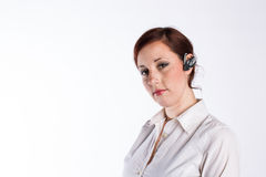 Woman with Bluetooth Headset. A young business woman with red hair and a serious look wears a bluetooth headset Royalty Free Stock Photos