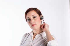 Woman with Bluetooth Headset. A young business woman twirls her red hair with a serious look wearing a bluetooth headset Stock Photography