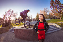Woman and BMX cyclist doing a stunt jump Royalty Free Stock Images